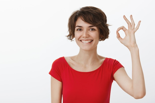 Mulher sorridente e satisfeita elogia o excelente trabalho, garante qualidade ou recomenda o produto com gesto de aprovação