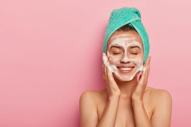 Mulher sorridente e satisfeita lava o rosto com gel de limpeza, passa sabonete na pele, mantém os olhos fechados, usa toalha enrolada na cabeça, tem corpo nu