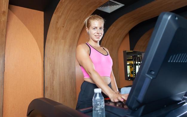 Mulher sorridente e saudável correndo na esteira na academia