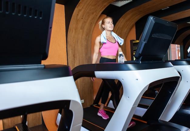 Mulher sorridente e saudável fazendo treinamento cardiovascular na esteira