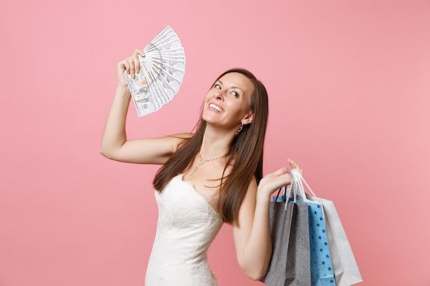 Mulher sorridente e sonhadora em um vestido branco olhando para cima segurando um pacote de muitos dólares, dinheiro em espécie, pacotes de sacolinhas multicoloridas com compras após as compras
