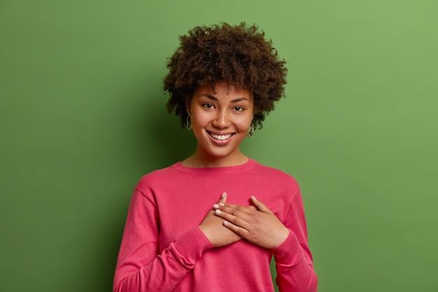 Mulher sorridente e terna aperta as mãos no peito em gesto de agradecimento e agradecimento, aprecia boas palavras e expressa gratidão, sente-se lisonjeada por receber um presente romântico, isolado na parede verde.