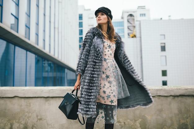 Mulher sorridente elegante andando pela cidade com casaco de pele quente e vestido de festa segurando uma bolsa de couro,