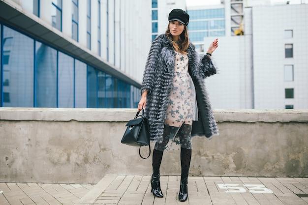 Mulher sorridente elegante caminhando pela cidade com um casaco de pele quente, inverno, clima frio, usando boné preto, vestido, botas, segurando uma bolsa de couro, tendência da moda de rua
