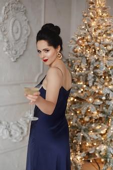 Mulher sorridente elegante em traje azul escuro posando com um copo de vinho no fundo de natal indoo.