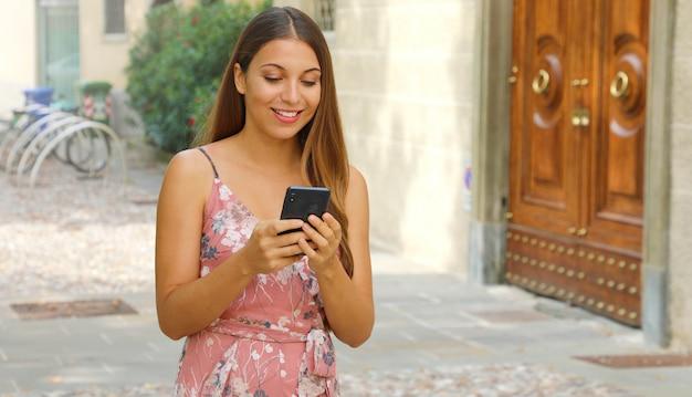 Mulher sorridente elegante turista digitando no celular na rua.