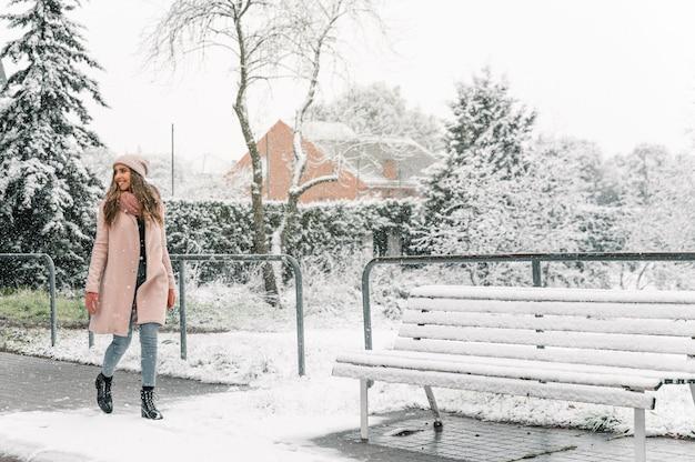 Mulher sorridente em agasalhos quentes caminhando ao longo do caminho em uma cidade nevada