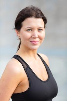 Mulher sorridente em athleisure posando ao ar livre