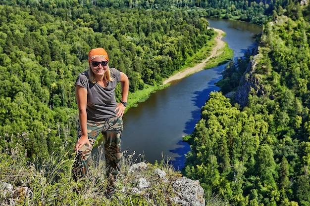 Mulher sorridente em bandana e óculos de sol fica no topo da montanha, no contexto do tranquilo rio da floresta fluindo abaixo, alpinista está envolvida em ecoturismo na rússia em um dia ensolarado de verão.