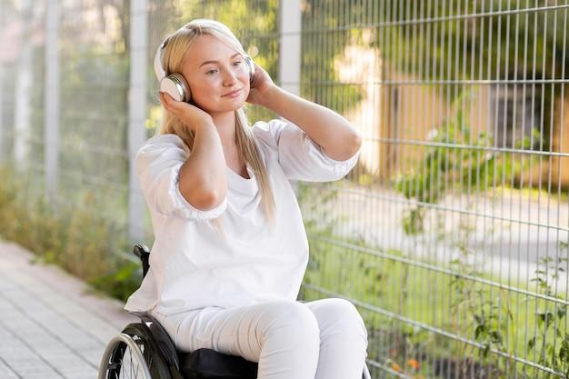 Mulher sorridente em cadeira de rodas com fones de ouvido