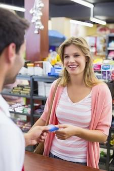 Mulher sorridente, em, caixa registradora, pagar, com, cartão crédito