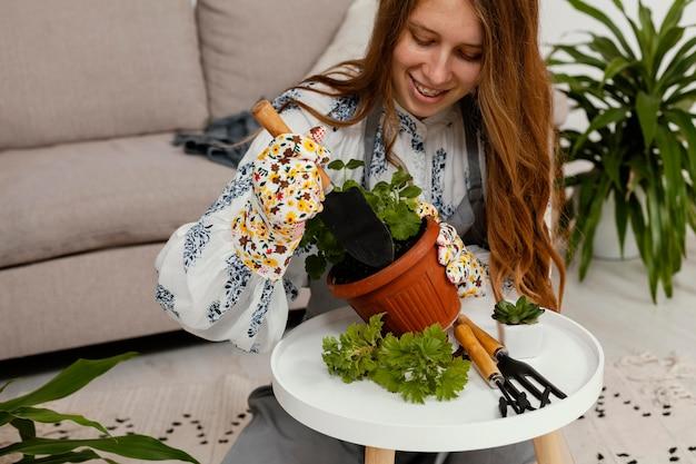 Mulher sorridente em casa com um vaso de plantas e ferramentas de jardinagem