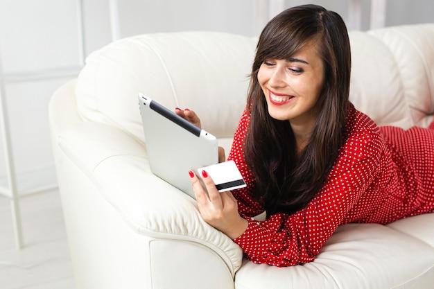 Mulher sorridente em casa pedindo itens à venda usando tablet e cartão de crédito