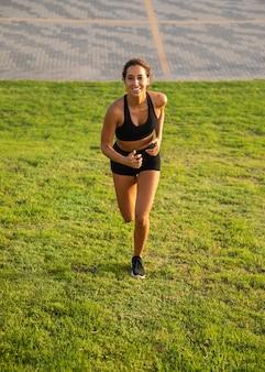 Mulher sorridente em cena completa correndo ao ar livre