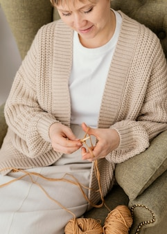 Mulher sorridente em close-up na poltrona tricotando