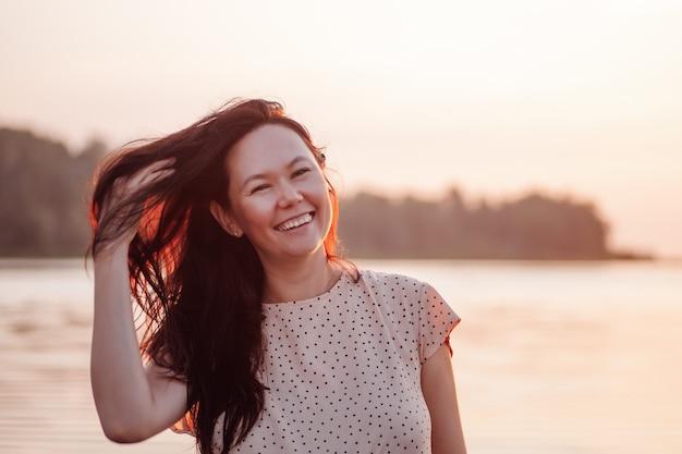 Mulher sorridente em closeup retrato ao ar livre de mulher asiática feliz contra o fundo da praia e do mar.