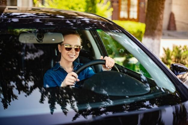 Mulher sorridente em copos dirige um carro escuro, segurando as mãos na roda