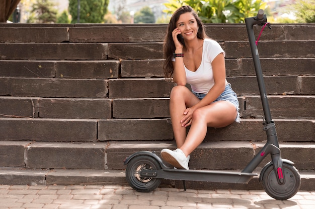 Mulher sorridente em degraus com scooter elétrico ao ar livre