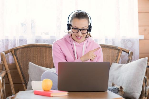 Mulher sorridente em fones de ouvido funciona remotamente com o computador portátil na casa de campo