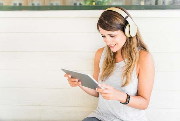 Mulher sorridente em fones de ouvido usando tablet