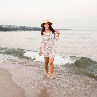 Mulher sorridente em foto completa caminhando na praia