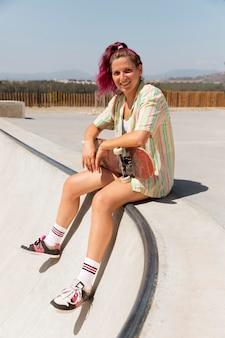 Mulher sorridente em foto completa com skate ao ar livre
