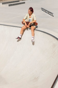 Mulher sorridente em foto completa com skate do lado de fora