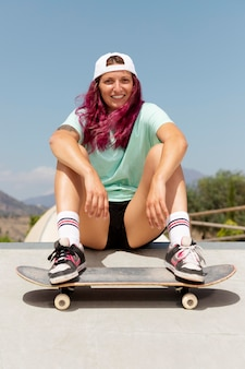 Mulher sorridente em foto completa com skate