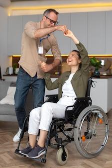 Mulher sorridente em foto completa sentada em uma cadeira de rodas