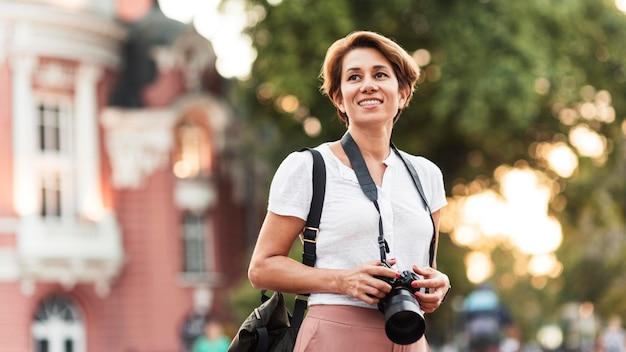 Mulher sorridente em foto média com câmera fotográfica