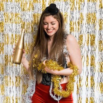 Mulher sorridente, em, noite, desgaste, com, garrafa, de, bebida, e, ouropel