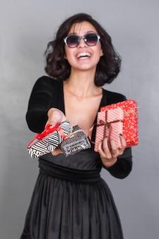 Mulher sorridente em óculos de sol com presentes