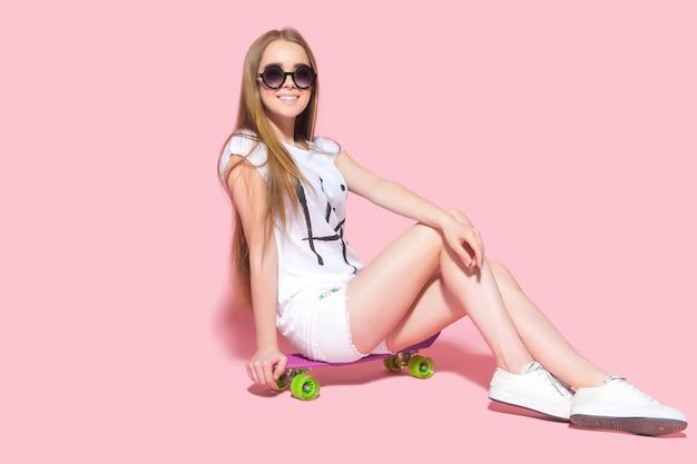 Mulher sorridente em óculos de sol no skate