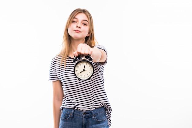 Mulher sorridente em óculos, segurando o relógio despertador