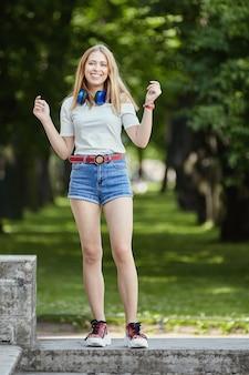 Mulher sorridente em parque público. alegre linda garota caucasiana de cerca de 20 anos em shorts e sapatos de plataforma está de pé no pavilhão do jardim.