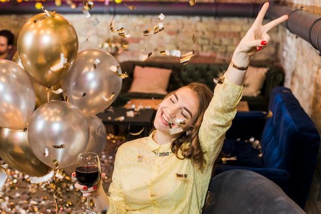 Mulher sorridente, em, partido, segurando, vidro vinho, desfrutando, em, partido