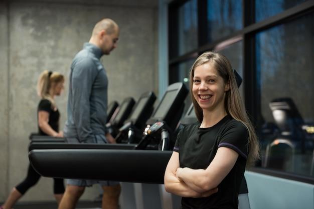 Mulher sorridente em pé com pessoas exercitando na esteira