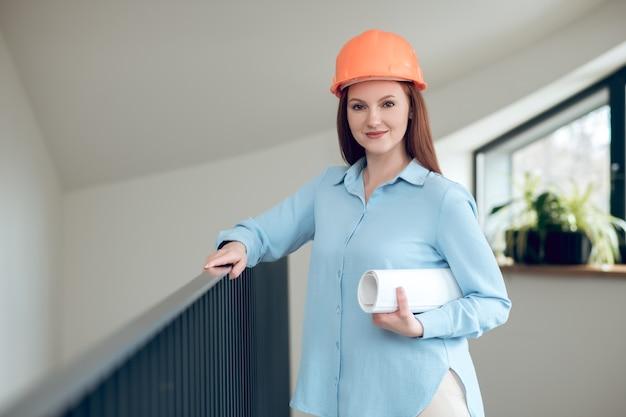 Mulher sorridente em pé dentro de casa com desenhos