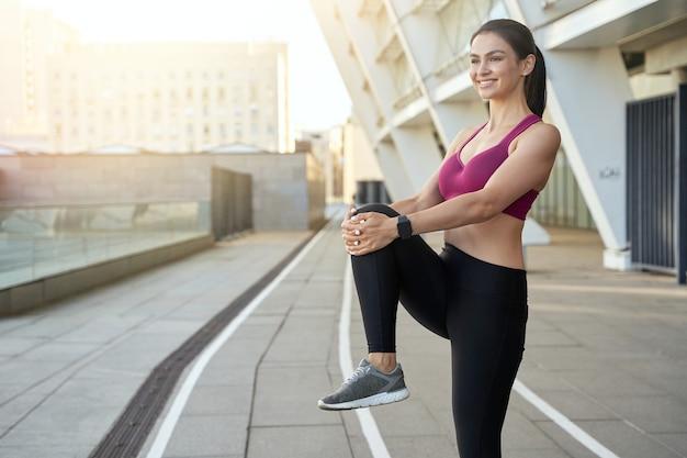 Mulher sorridente em pé e esticando a perna antes de correr