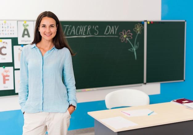 Mulher sorridente em pé na sala de aula