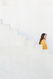 Mulher sorridente em pé perto de degraus brancos