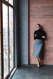 Mulher sorridente em pé próximo à parede