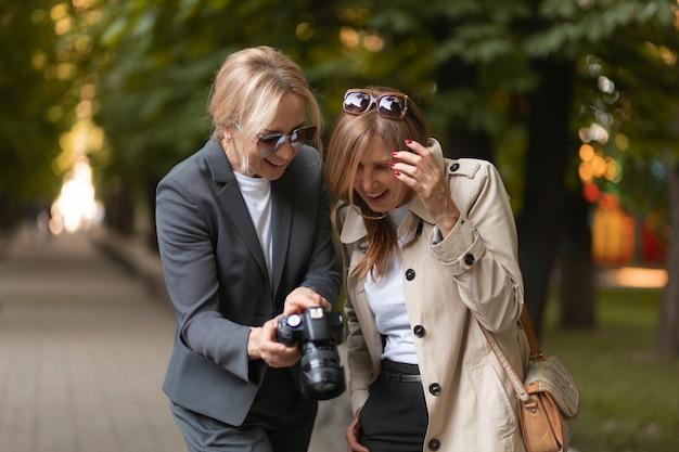 Mulher sorridente em plano médio com câmera fotográfica