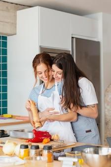 Mulher sorridente em plano médio cozinhando