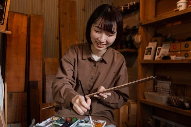 Mulher sorridente em plano médio pintando