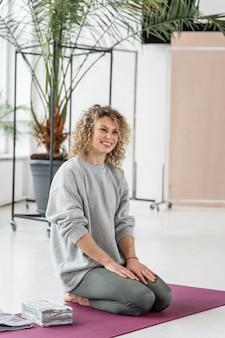 Mulher sorridente em plena cena no tapete de ioga