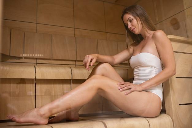 Mulher sorridente em pleno tiro na sauna