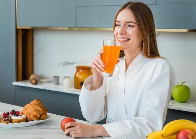 Mulher sorridente em roupão bebendo suco