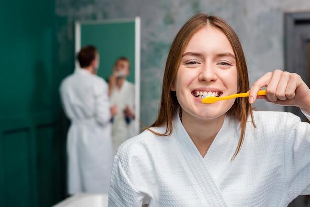 Mulher sorridente em roupão, escovando os dentes