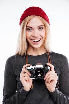 Mulher sorridente em roupas casuais em pé e segurando a câmera retro
